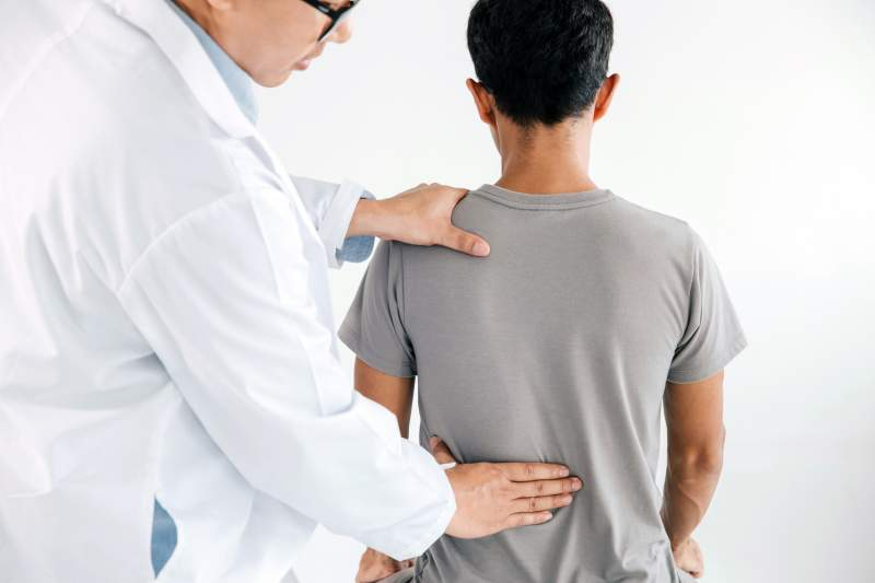 Physiotherapist doing healing treatment on man's back