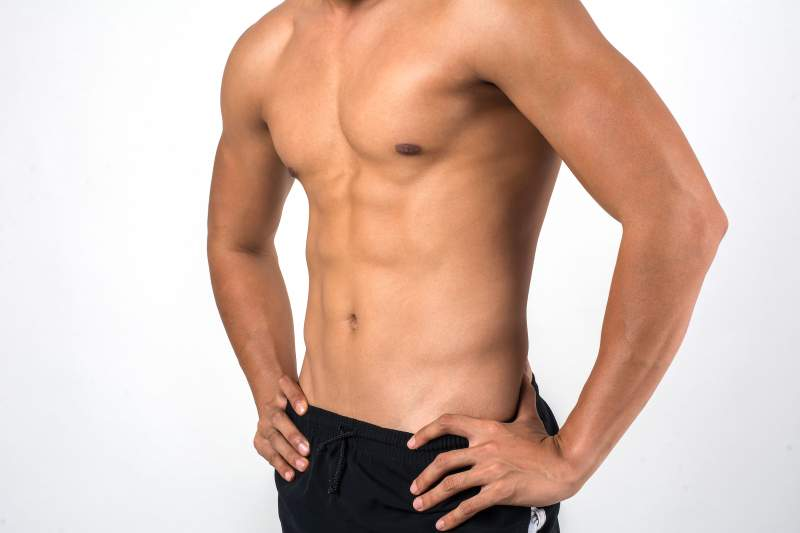 Muscular man showing six pack abs