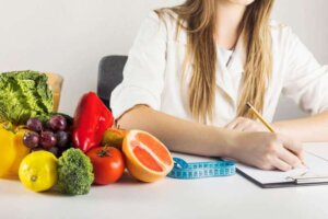 dietician-s-hand-writing-clipboard-with-healthy-food-desk