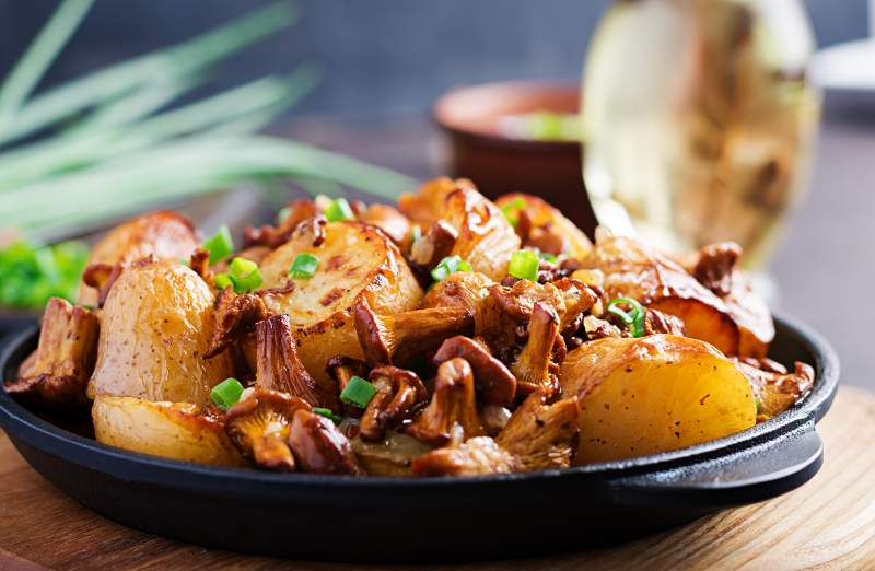 Baked potatoes with garlic, herbs and fried chanterelles in a cast iron skillet