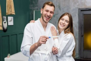 Happy couple in bathrobes holding pregnancy test