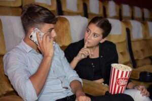 Young man talking on mobile phone during see movie