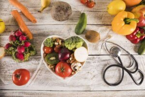 Heart shape container with healthy vegetables near stethoscope
