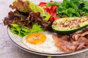 Plate with a keto diet food. fried egg, bacon, avocado, arugula and strawberries