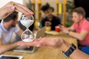 Human hand holding hourglass in front of people