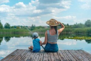 woman-and-boy-sitting-on-dock-holding-fishing-rod