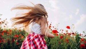 faceless-girl-picking-up-flowers-in-field