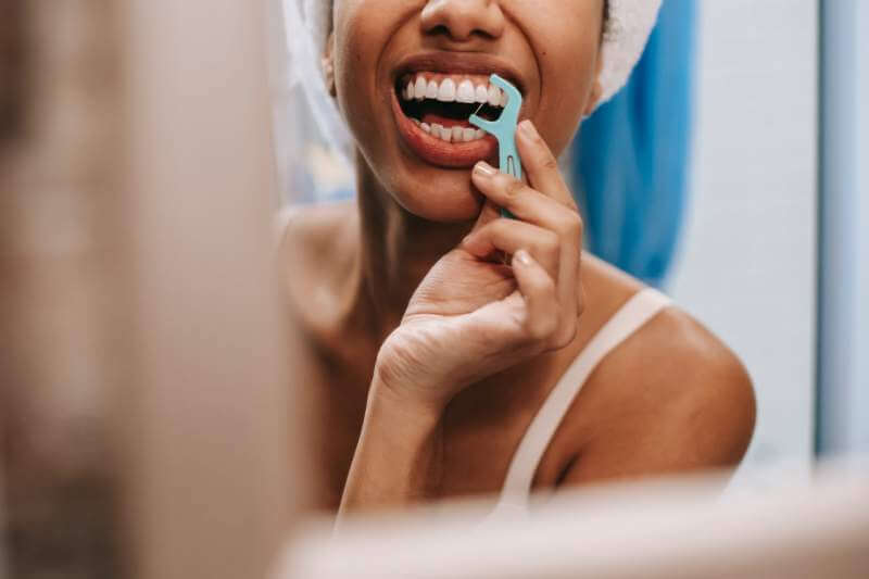 reflection-of-woman-cleaning-teeth