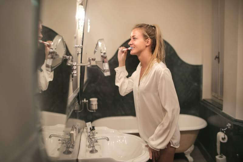 young-woman-cleaning-teeth-in-bathroom